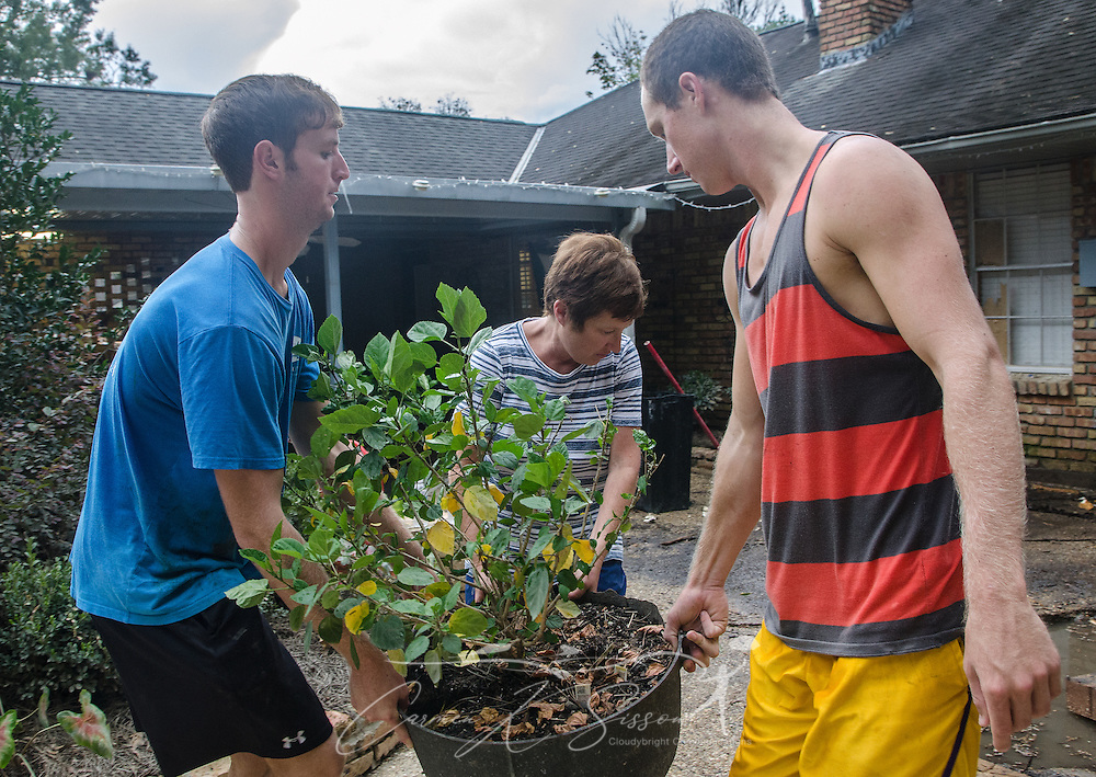 John Whitehead and Jacob Whitehead help their mother, Zanie Whitehead, carry a potted plant, Sept. 4, 2016, in Denham Springs, Louisiana. John Whitehead used his kayak to rescue many of his neighbors after heavy rain caused extended flooding in mid-August. The boys attend Louisiana State University, and the family attends Istrouma Baptist Church in Baton Rouge. (Photo by Carmen K. Sisson)