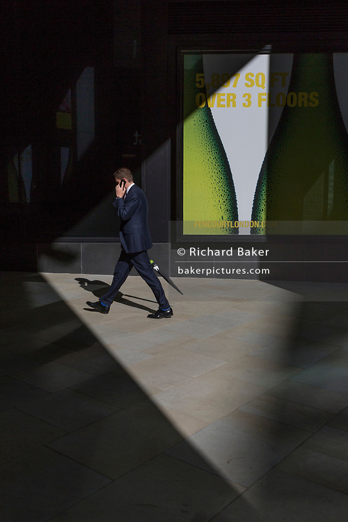 Business person walk through sunlight in the City of London, the capital's financial heart (aka The Square Mile), on 26th September 2018, in London, England.