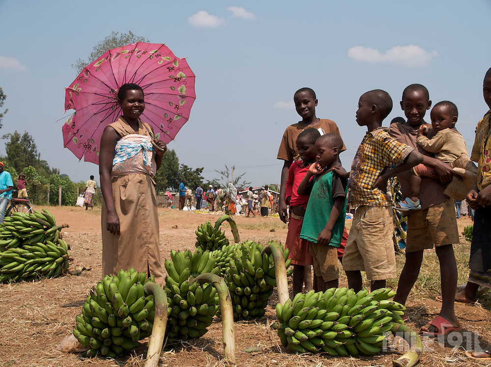 A lady selling bananas at the market shelters from the sun under a pink umbrella, Rwanda.