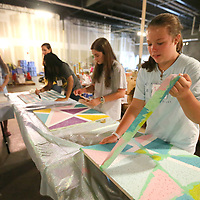 Julia Jane Averette, 12, of Tupelo, removes tape from her painted bulletin board art project she has been working on during SHINE Camp this week at HealthWorks in Tupelo. SHINE Camp is week long camp put on by the Junior Auxiliary of Tupelo for upcoming middle school girls that promotes positive self-esteem through devotions, drama, art, physical excerise and group discussions.