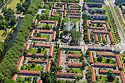 Nederland, Noord-Holland, Amsterdam, 14-06-2012; Woonbuurt in Slotervaart, eengezinswoningen gebouwd volgens ruim opgezet stratenplan. Burgemeester Rendorpstraat (vlnr), links de Burgemeester Van Tienhovengracht, rechts Burgemeester Roellstraat . De doopsgezinde kerk De Olijftak is nu in gebruik als Moskee El Hijra (Marokkaans). De moordenaar Mohammed Bouyeri van Theo van Gogh woonde in deze buurt. ..De wijk is onderdeel van de Westelijke Tuinsteden, gerealiseerd op basis van het Algemeen Uitbreidingsplan voor Amsterdam (AUP, 1935). Voorbeeld van het Nieuwe Bouwen, open bebouwing in stroken, langwerpige bouwblokken afgewisseld met groenstroken. .Residential district Slotervaart, one of the western garden cities of Amsterdam-west..  Constructed on the basis of the General Extension Plan for Amsterdam (AUP, 1935). Example of the New Building (het Nieuwe Bouwen), detached in strips, oblong housing blocks alternated with green areas, built in fifties and sixties of the 20th century. Church is now a mosque..luchtfoto (toeslag), aerial photo (additional fee required).foto/photo Siebe Swart
