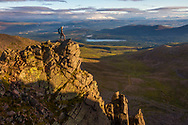 A mountain hiker at sunrise overlooking Coire an t-Sneachda in the Cairngorms National Park, Scotland.