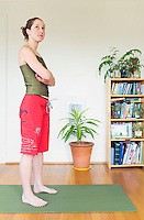 Portrait of a late 20's woman standing on her yoga mat in her apartment...Model Release: 20070608_MR_A