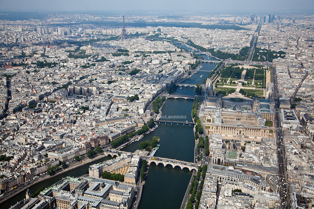 Along the right side of the Seine river lies the Louvre Museum, the Tuileries Garden, and the well-known Champs-Elysees avenue leading to the Arc du Triomphe and the Grand Arche de La Defense. To the left of the Seine lies the Eiffel Tower.