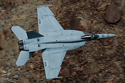 Boeing F/A-18E Super Hornet from United States Navy squadron VFA-25 Fist of the Fleet (AG 406) flies low level through the Jedi Transition, Star Wars Canyon, Death Valley National Park, California, United States of America