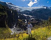 A hiker in a field of yellow flowers admires water falling from an ice cap in Rob Roy Valley, Mount Aspiring National Park, Southern Alps, South Island, New Zealand. In 1990, UNESCO honored Te Wahipounamu - South West New Zealand as a World Heritage Area.