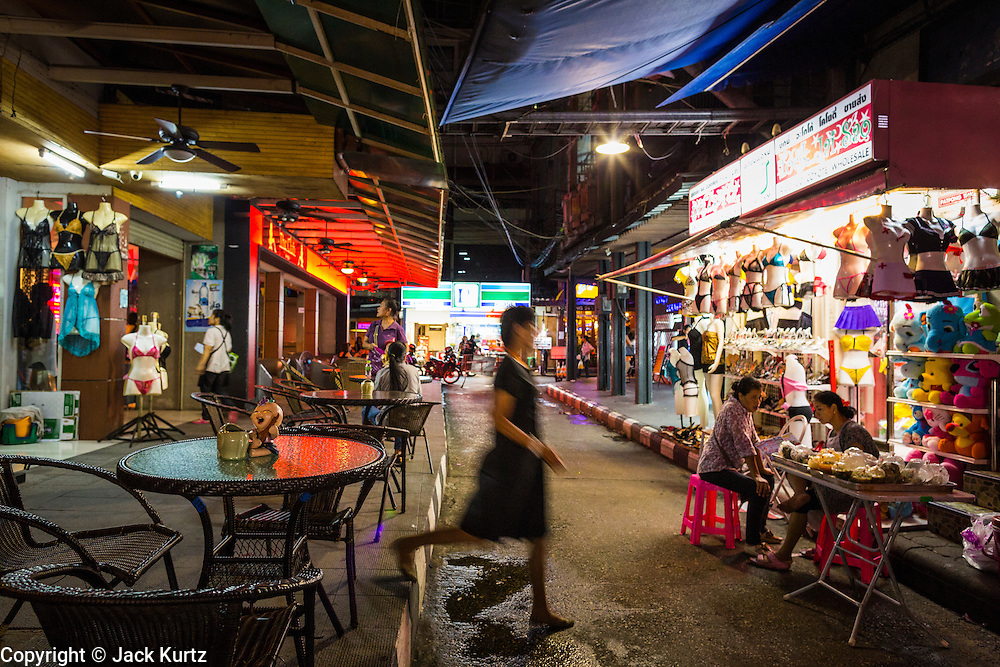 4 JUNE 2013 - BANGKOK, THAILAND:  A woman crosses a street in the Patpong Night Bazaar in Bangkok. Patpong was one of Bangkok's notorious red light districts but has been made over as a night market selling clothes, watches and Thai handicrafts. The old sex oriented businesses still exist but the area is now better known for its night shopping.      PHOTO BY JACK KURTZ