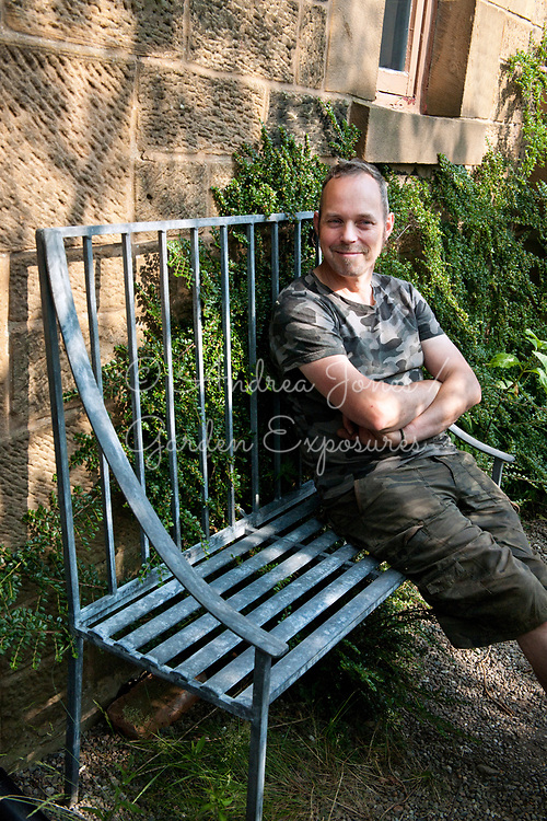 Euan Sutherland sitting on the 'English Garden' magazine competition prize winning seat