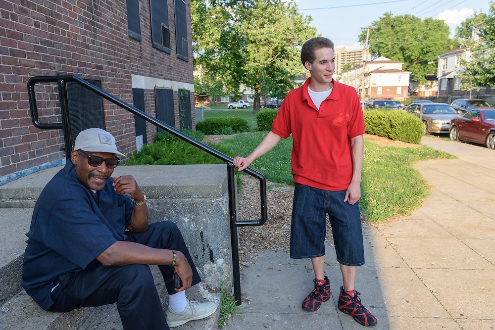 Eddie Woods, director of Street Peace: No More Red Dots, waits for Norman Martin, his childhood friend and Street Peace's team coordinator, with his son Darin Woods, Monday, June 20, 2016 on the steps of the Baxter Community Center in the Beecher Terrace neighborhood. (Photo by Brian Bohannon)
