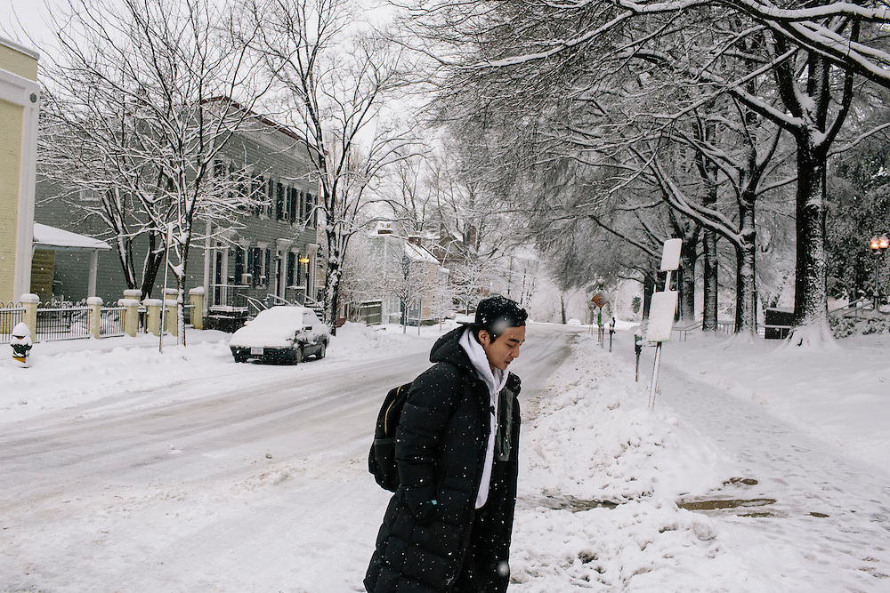 """Roy Kim, a Georgetown University sophomore, walks to the library during a snow storm to continue working on recording an English language track for his recording class. Kim became a South Korean pop star after winning Superstar K4, his country's version of American Idol. Kim says he is able to have a private life in the US without much fan interference. """"They know my life here should be respected,"""" Kim said. """"That makes the relationship between me and my fans more tight."""""""