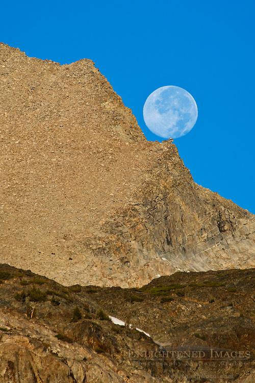 Full moon setting over mountains; near Tioga Pass; Eastern Sierra; California