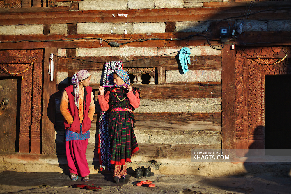 Two friends chatting outside a temple while enjoying the sunset at a village in Kullu