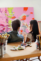 Couple Discussing Painting in Artist's Studio