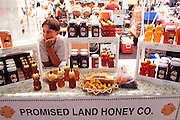 Young boy selliing honey at a farmers market in Portland, Oregon.