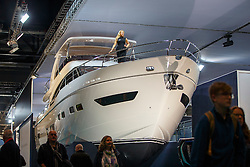 © Licensed to London News Pictures. 06/01/2017. London, UK. Sailing enthusiasts visit the London Boat Show at ExCel London whilst a model posing on a Princess yatch in the background on Friday, 6 January 2017. Until the 15th of January the London Boat Show will showcase, demonstrate and sell maritime equipment ranging from luxury yachts to dinghies. Photo credit: Tolga Akmen/LNP