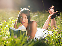 Young woman lying in meadow holding book and apple