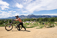 Chance Leingang of Fort Collins walks back up to the top of the Slopestyle track at the popular Valmont Bike Park in Boulder, CO. © Brett Wilhelm
