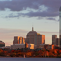 Boston skyline photography showing historic landmarks such as brownstone buildings, old Hancock building and new John Hancock Tower along the Charles River on a beautiful cloudy autumn late afternoon in October.<br />