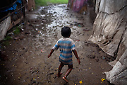 A young boy is running home under heavy rain in the impoverished Oriya Basti colony, Bhopal, Madhya Pradesh, India, near the abandoned Union Carbide (now DOW Chemical) industrial complex.