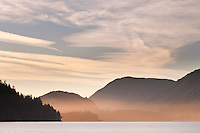 The sunrise features gold and pink colors as it rises over the mountains behind Lake Cowichan on Vancouver Island, BC