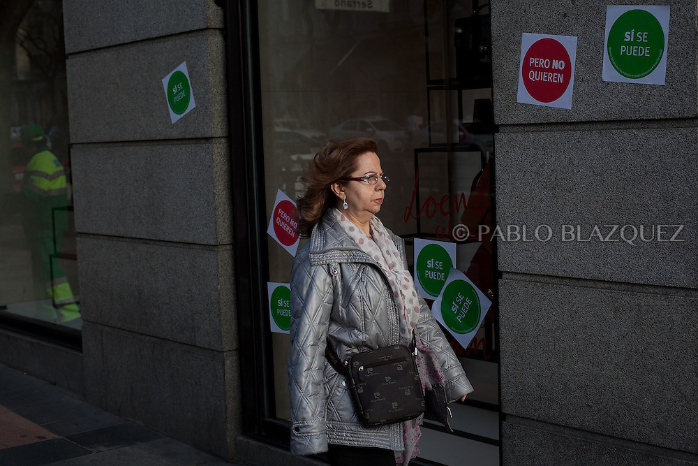 A woman walks by a shop while stickers reading 'Yes we can, but they don't want' are seen pasted on a window display during an 'escrache' near the house of Spain's President of Parliament Jesus Posadas on April12, 2013 in Madrid, Spain. The Mortgage Holders Platform (PAH) and other anti evictions organizations have been organizing 'escraches' for several weeks under the slogan 'There are lives at risk' to claim the vote for a Popular Legislative Initiative (ILP) to stop evictions and facilitate social rent, outside Popular Party deputies' houses and offices. 'Escraches' are a form of peaceful protest that were used in Argentine in 1995 to publically denounce pardoned members of the dictatorship for their crimes at their doorsteps.
