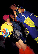 Two ravers dressed in fluorescent clothing with Pikachu backpack, red, furry boots and horn, U.K, 1990s.