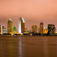 San Diego skyline at night with  downtown city buildings along San Diego Bay.