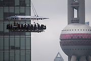 SHANGHAI, CHINA - JUNE 27: (CHINA OUT) <br /> <br /> Restaurant In The Sky<br /> <br /> Diners are suspended from a crane as they enjoy a meal organized by the 'Dinner in the Sky' over Lujiazui Financial District on June 27, 2014 in Shanghai, China. The unusual table plan can accommodate up to 22 diners and each meal lasts about 50 minutes including hoisting customers up and down. Costs range from 1,888 to 8,888 yuan (302 - 1,422 USD) per person depending on choice of food. The hotel will offer 14 sittings, serving up to 308 people in three days. It will also operate in September and October. All diners are secured in their seats with waiters and cooks taking safety harnesses similar to those used in Bungee jumping.<br /> ©Exclusivepix