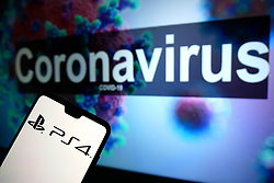 The Playstation 4 logo seen displayed on a mobile phone with an illustrative model of the Coronavirus displayed on a monitor in the background. Photo credit should read: James Warwick/EMPICS Entertainment