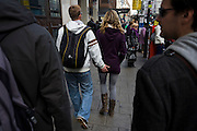 Surrounded by the public, a young man walks along feeling his partner's bottom in a busy London street.