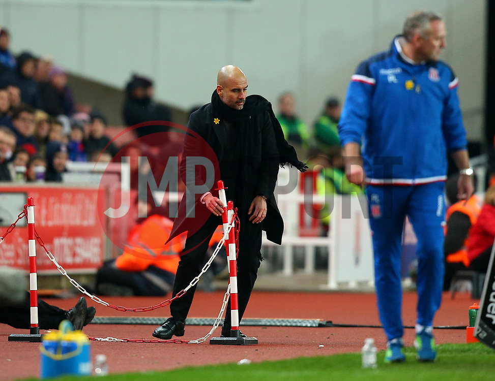 Manchester City manager Pep Guardiola tries to fix a chained cordon that Kyle Walker of Manchester City had kicked over - Mandatory by-line: Robbie Stephenson/JMP - 12/03/2018 - FOOTBALL - Bet365 Stadium - Stoke-on-Trent, England - Stoke City v Manchester City - Premier League