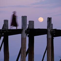 A buddhist monk greets the moonrise at Ubein's bridge in Mandalay, Myanmar.