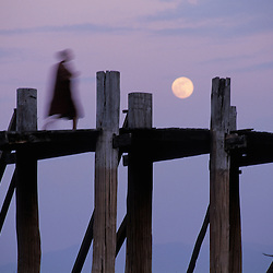 A buddhist monk greets the moonrise at Ubein's bridge in Mandalay, Myanmar.