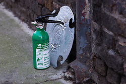 © Licensed to London News Pictures. 22/12/2013. London, UK. A fire extinguisher on the side of the street at the entrance to Unit 10, Studio Spaces in Pennington Street, East London. Around 16 emergency vehicles attended an incident in the early hours of 22 December 2013 where a 'Santa Stamp' rave event was being held and two people were stabbed, windows were broken and objects were thrown from windows on the top floor. Photo credit : Vickie Flores/LNP