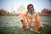 Agra, a sadhu sits on the banks of the Yamuna river with the Taj Mahal in the background.