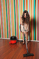 Young woman cleaning hardwood floor with vacuum cleaner