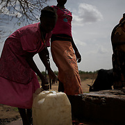 April 28, 2012 - Buram, Nuba Mountains, South Kordofan, Sudan: Nuba women take water out of a borehole in the center of Buram village in South Kordofan's Nuba Mountains...Since the 6th of June 2011, the Sudan's Army Forces (SAF) initiated, under direct orders from President Bashir, an attack campaign against civil areas throughout the South Kordofan's province. Hundreds have been killed and many more injured...Local residents, of Nuba origin, have since lived in fear and the majority moved from their homes to caves in the nearby mountains. Others chose to find refuge in South Sudan, driven by the lack of food cause by the agriculture production halt due to the constant bombardments of rural areas. (Paulo Nunes dos Santos/Polaris)