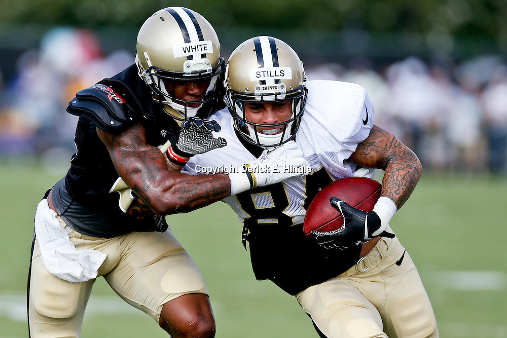 Aug 3, 2013; Metairie, LA, USA; New Orleans Saints wide receiver Kenny Stills (84) is tackles by cornerback Corey White (24) during a scrimmage at the team training facility. Mandatory Credit: Derick E. Hingle-USA TODAY Sports