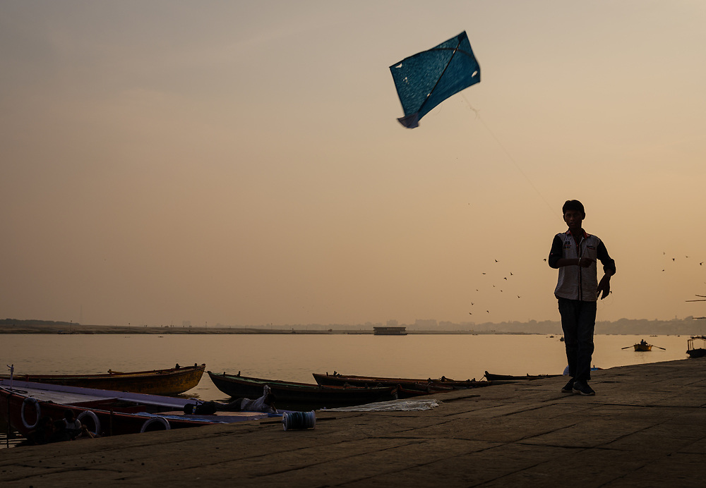 Varanasi, INDIA - CIRCA NOVEMBER 2018: Young kids flying kites over the ghats of Ganges River in Varanasi. Varanasi is the spiritual capital of India, the holiest of the seven sacred cities and with that one the most frequented places for Sadhus.