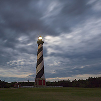 Full moon hides behind clouds, above Cape Hatteras Lighthouse. Cape Hatteras National Seashore, NC