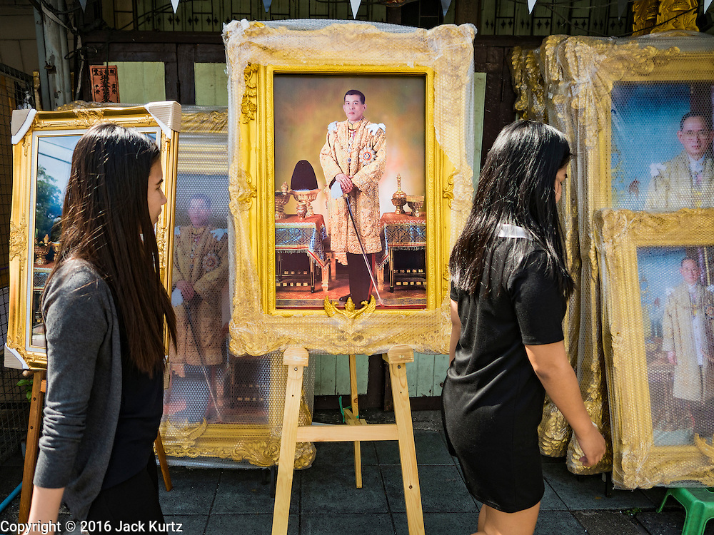 01 DECEMBER 2016 - BANGKOK, THAILAND: Women wearing black mourning clothes walk past a portrait of HRH Crown Prince Maha Vajiralongkorn, who will soon be the new King of Thailand. Thailand's parliamentary body, the National Legislative Assembly, invited HRH Crown Prince Maha Vajiralongkorn to be king following the death of the Crown Prince's father, Bhumibol Adulyadej, the Late King of Thailand. The invitation marked the formal beginning of the process of naming the new King, although Crown Prince Vajiralongkorn was the heir apparent and Bhumibol's appointed successor. Shops that sell royal paraphernalia are now selling new portraits of  Crown Prince Vajiralongkorn which will be displayed alongside portraits of his late father. King Bhumipol died on Oct 13.      PHOTO BY JACK KURTZ