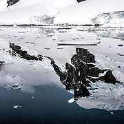 Glassy waters reflec the rugged landscape of Cuverville Island on the western side of the Antarctic Peninsula.