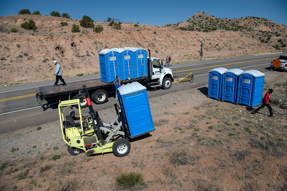 em041317f/jnorth/Workers with Santa Fe Waste Services set up 36 portable toilets along Madina Road and other roads leading to the Santuario de Chimayo Thursday April 13, 2017. Hundreds of people were making their pilgrimage to the Northern New Mexico church on Thursday, thousands will on Good Friday.   (Eddie Moore/Albuquerque Journal