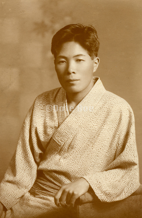 Studio portrait of an Asian man in traditional dress.
