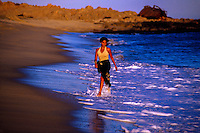 Mexican woman walking on the beach, Los Cabos, Baja California, Mexico