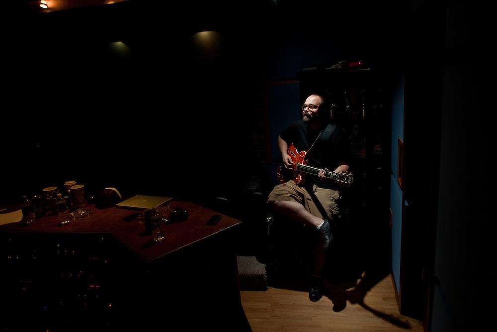 A man (B Pelon) plays an electric guitar in a recording studio.