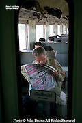 A man is reading a newspaper on a Bangkok bound passenger train in Ubon Ratchathani Province, Thailand.