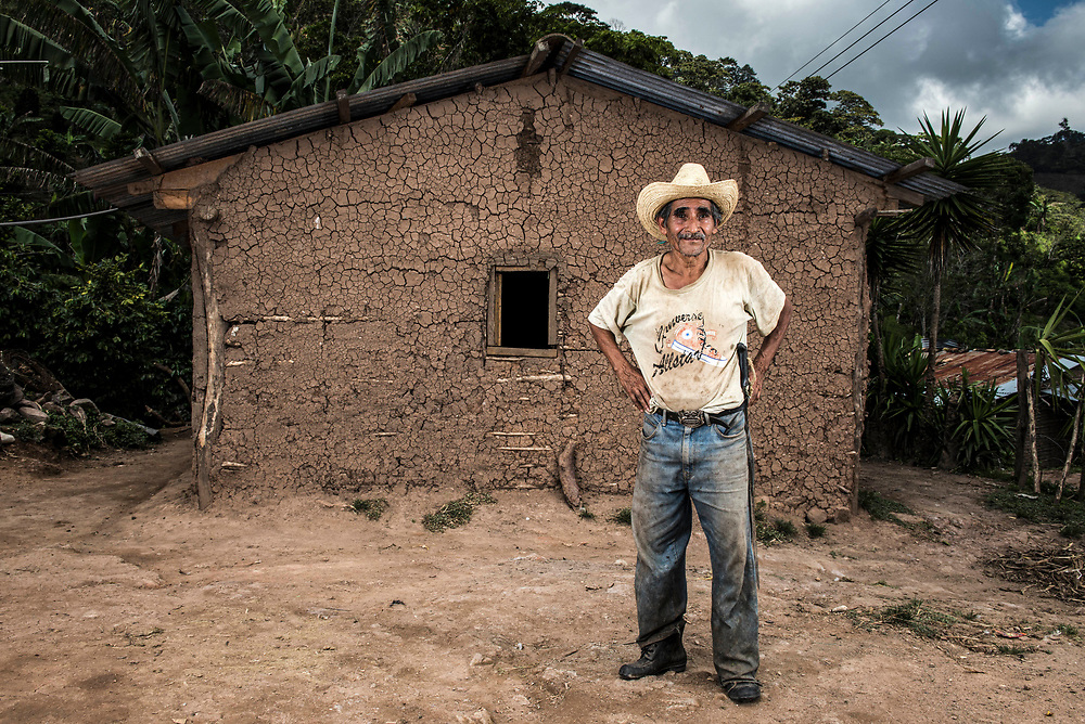 A man poses for a photograph in front of his adobe home in Pueblo Veracruz Oct 7, 2014. Central American Medical Outreach visit his family and two others who all live nearby on occasion to make sure they are doing well.