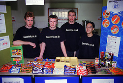 Multiracial group of male youths standing behind sweet shop counter run as Young Enterprise business venture,