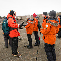 Naturalist Zach Brown speaks with guests during an exploration of a gentoo penguin colony on Barrientos Island.